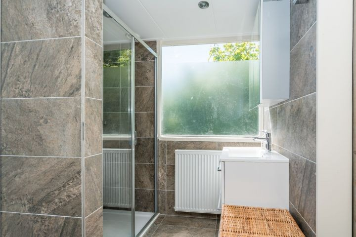 Das moderne, neue Badezimmer mit Dusche und Waschbecken