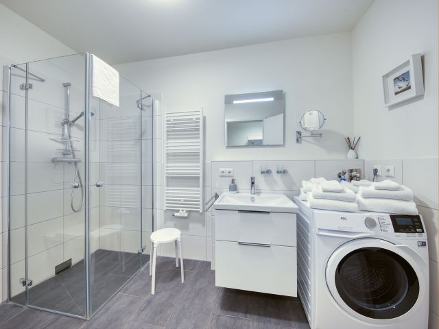 modernes Bad mit ebenerdiger Dusche und Waschtrockner