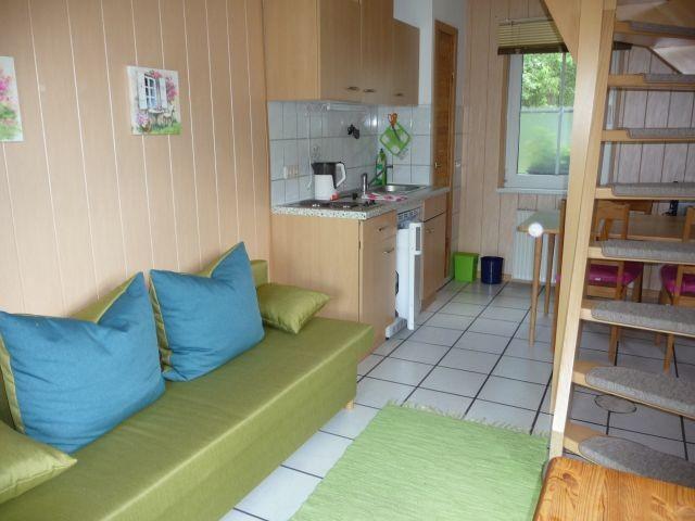 der Eingangsbereich mit Schlafsofa und SAT-TV und Küchenzeile mit Esstisch