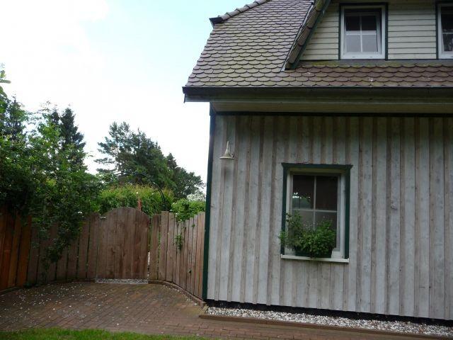 kleinere Fw in linker Häuschenhälfte mit Holztor abgetrennt von d Auffahrt