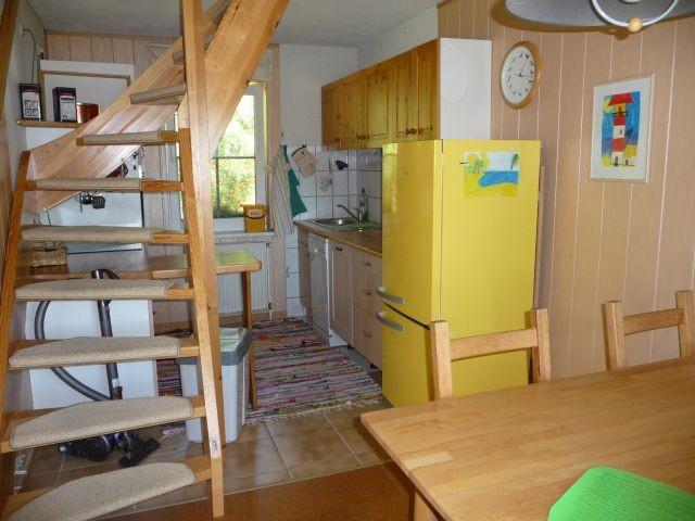 Blick vom Essbereich in den Küchenbereich mit Geschirrspüler, komfortable Treppe ins Obergeschoss zu Schlafbereich un Bad