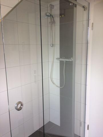 Badezimmer mit ebenerdiger großer Dusche und Handtüchern