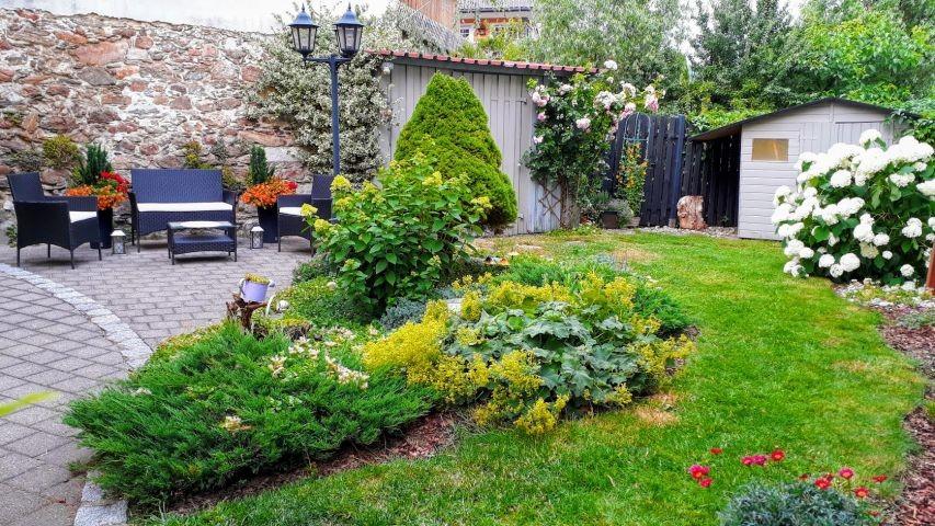 Hoch eingezäunter Garten im Sommer