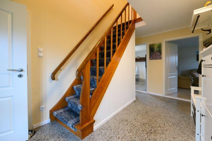 geschlossene Holztreppe mit Teppichstufen ins OG