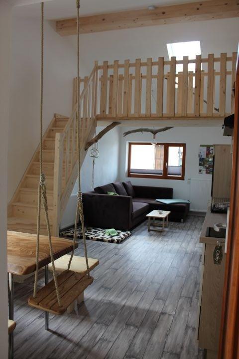 Der geräumige, helle Wohnraum mit Schaukel am Esstisch und Aufgang zur Galerie