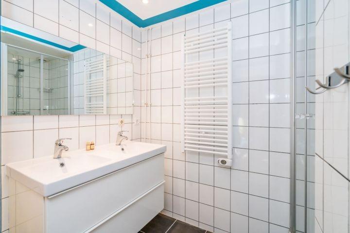 Das Bad mit Dusche und einem doppelten Waschbecken