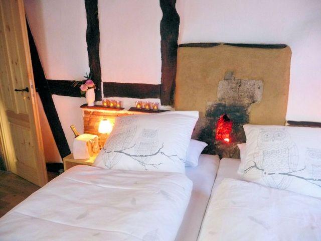 Es gibt im Haus zwei Doppel-Schlafzimmer. Hier sehen Sie die Romantik-Stube. Trotz der Kernsanierung des Bauernhauses haben wir mit viel Aufwand diese Wand im OG erhalten, damit die Gäste den beleuchteten, alten Kamin über ihrem Doppelbett haben.