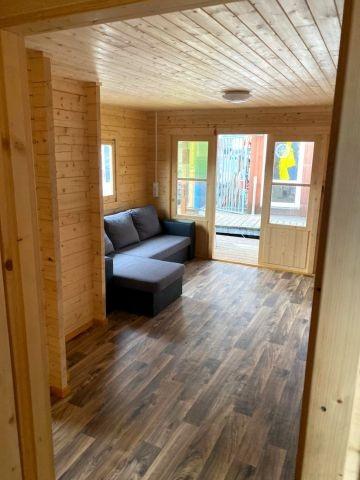 Wohnbereich mit Schlafsofa, Esstisch und Stühlen