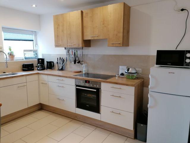 Küche mit Geschirrspüler, Herd, Backofen, Kühlschrank und Gefrierbox