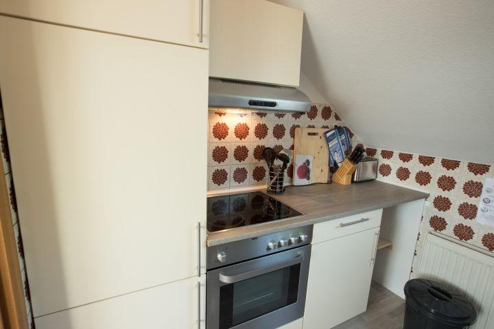 Küche mit Kühlschrank, Backofen, Herd und Toaster
