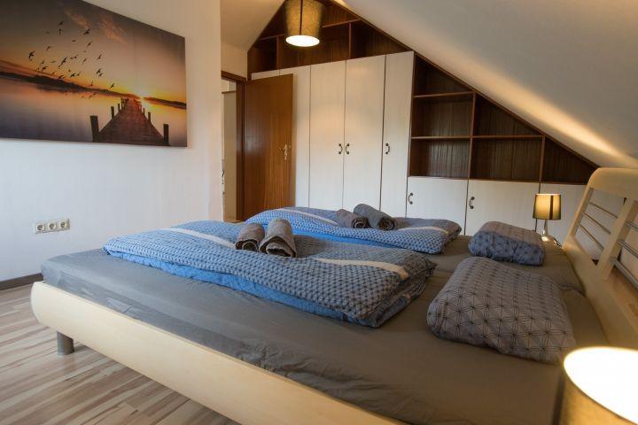 Schlafzimmer 1 mit großem Doppelbett (1,80m * 2m) und Blick auf Kleiderschrank