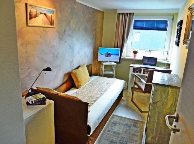 Einzelzimmer mit Schreibtisch und TV