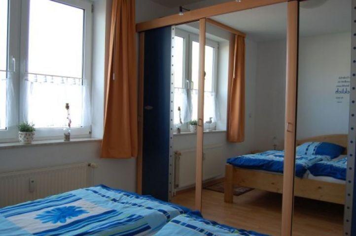 Schlafzimmer mit großem Kleiderschrank und bequemen Doppelbett