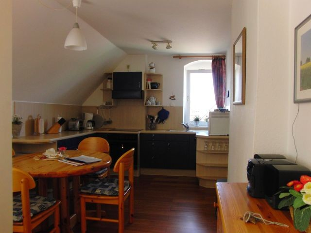 Esstisch mit Stühlen und moderner Einbauküche
