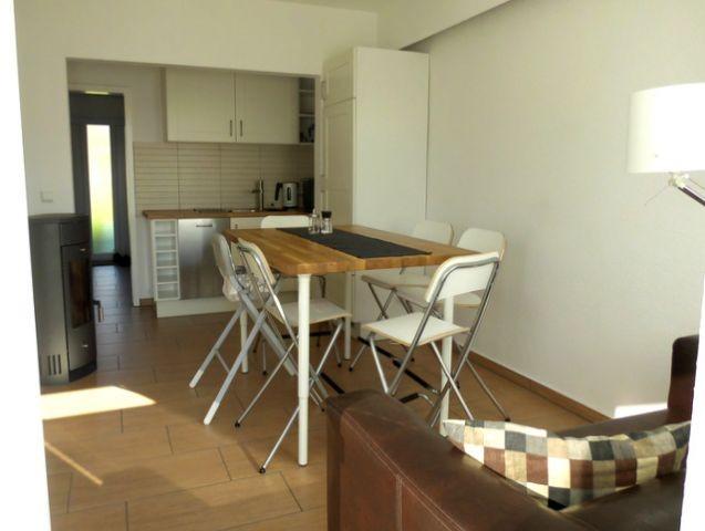 Wohnraum mit Kamin und integrierter Küche und Esstisch