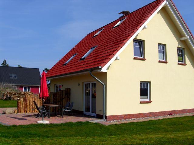Ferienhaus Kranichnest, Terrasse mit Gartenstühlen, Sonnenschirm und Grill